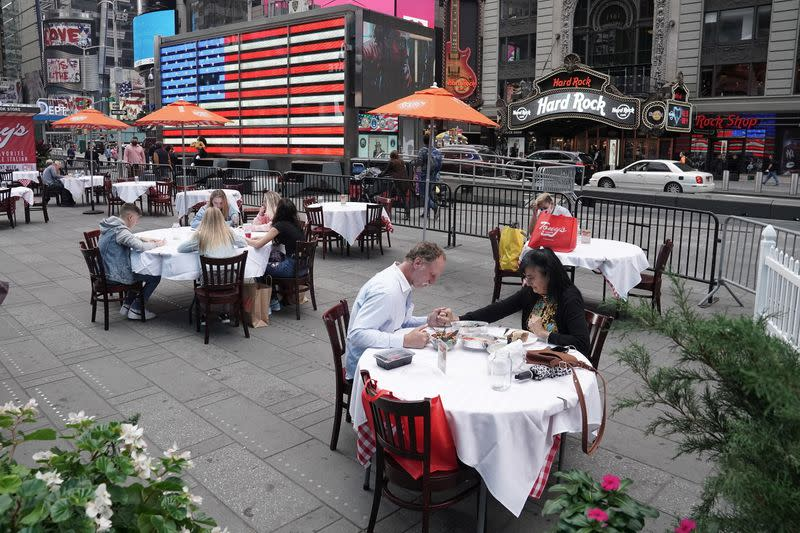 A man and woman hold hands as they say grace before dining outside at a pop up restaurant in New York