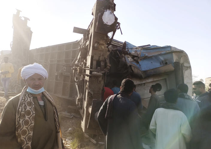 Egyptians look for remains of victims around mangled train carriages at the scene of a train accident in Sohag, Egypt, Friday, March 26, 2021. Egyptian officials say two trains collided in southern Egypt in the latest in a series of deadly accidents along Egypt's troubled rail system, which has been plagued by poor maintenance and management. (AP Photo)
