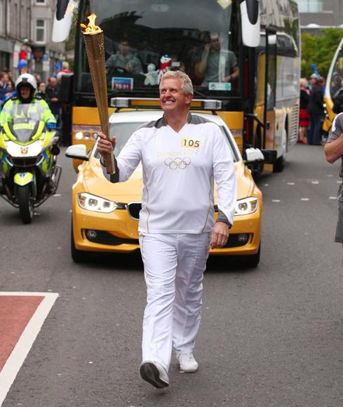 Scottish golfer Colin Montgomerie carries the Olympic Flame on the Torch Relay leg between Cults and Aberdeen on day 24 of the London 2012 Olympic Torch Relay on June 11, 2012 in Scotland. The Olympic Flame is now on day 24 of a 70-day relay involving 8,000 torchbearers covering 8,000 miles.  (Photo by LOCOG via Getty Images)
