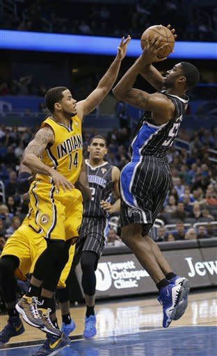 Orlando Magic's E'Twaun Moore shoots over Indiana Pacers' D.J. Augustin (14) during the first half of an NBA basketball game, Friday, March 8, 2013, in Orlando, Fla. (AP Photo/John Raoux)
