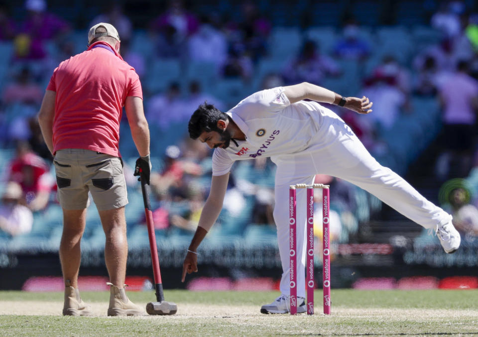 Indian bowler Jasprit Bumrah points to the pitch for a groundsman to work on during play on day three of the third cricket test between India and Australia at the Sydney Cricket Ground, Sydney, Australia, Saturday, Jan. 9, 2021. (AP Photo/Rick Rycroft)