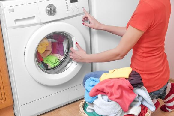 A woman setting her washing machine with a laundry basket full of clothes next to her.