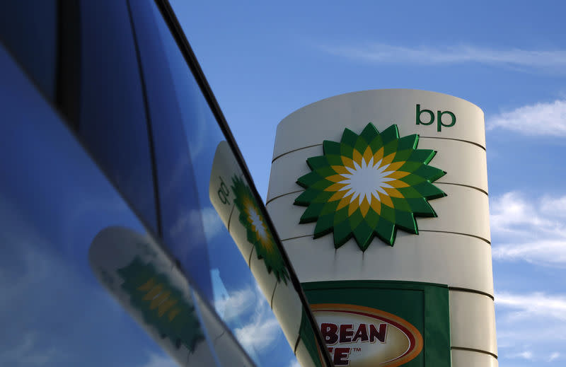 A BP logo is reflected in a car window at a petrol station in London