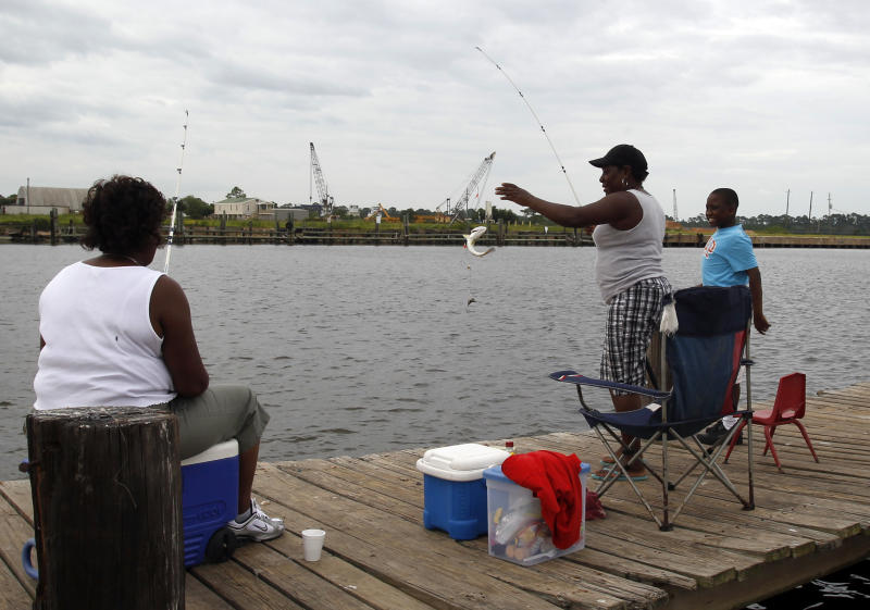 Renay Orr, left, and Taytay Harris watch as Franchy Coleman, center, reels in a Trout in Bayou La Batre, Ala. on Monday, Aug. 27, 2012. The National Hurricane Center predicted Isaac would grow to a Category 1 hurricane over the warm Gulf and possibly hit late Tuesday somewhere along a roughly 300-mile (500-kilometer) stretch from the bayous southwest of New Orleans to the Florida Panhandle.The size of the warning area and the storm's wide bands of rain and wind prompted emergency declarations in four states, and hurricane-tested residents were boarding up homes, stocking up on food and water or getting ready to evacuate. (AP Photo/Butch Dill)