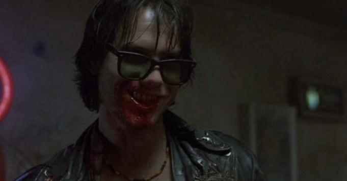Man in sunglasses smiles while mouth is covered in blood