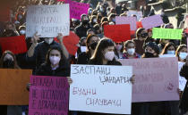 """Young people wearing face masks carry banners during a protest march through downtown Skopje, North Macedonia, on Wednesday, Feb. 3, 2021. Several hundred mostly young people have gathered in front of the North Macedonia's Interior ministry on Wednesday to protest sexual harassment of women on social media and policy of impunity for that kind of violence. Some of the banners read in Macedonian: """"The Victim is never guilty!"""", """"Cops asleep - Rapists awake"""", """"State not acting is state raping"""", """"Public Room is a criminal act"""". (AP Photo/Boris Grdanoski)"""