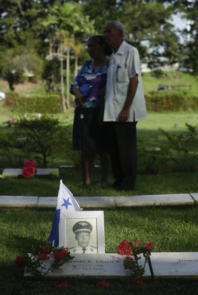 A photograph sits  on the grave of a military person who died during the 1989 U.S. military invasion that ousted Panama's strongman Manuel Noriega, as a couple attends a ceremony on the 30th anniversary of the invasion at Jardin de Paz cemetery in Panama City, Friday, Dec. 20, 2019. According to official figures, 300 Panamanian soldiers and 214 civilians died during the invasion, though the number remains controversial and human rights groups believe it is much higher. Twenty-three U.S. soldiers also perished. (AP Photo/Arnulfo Franco)