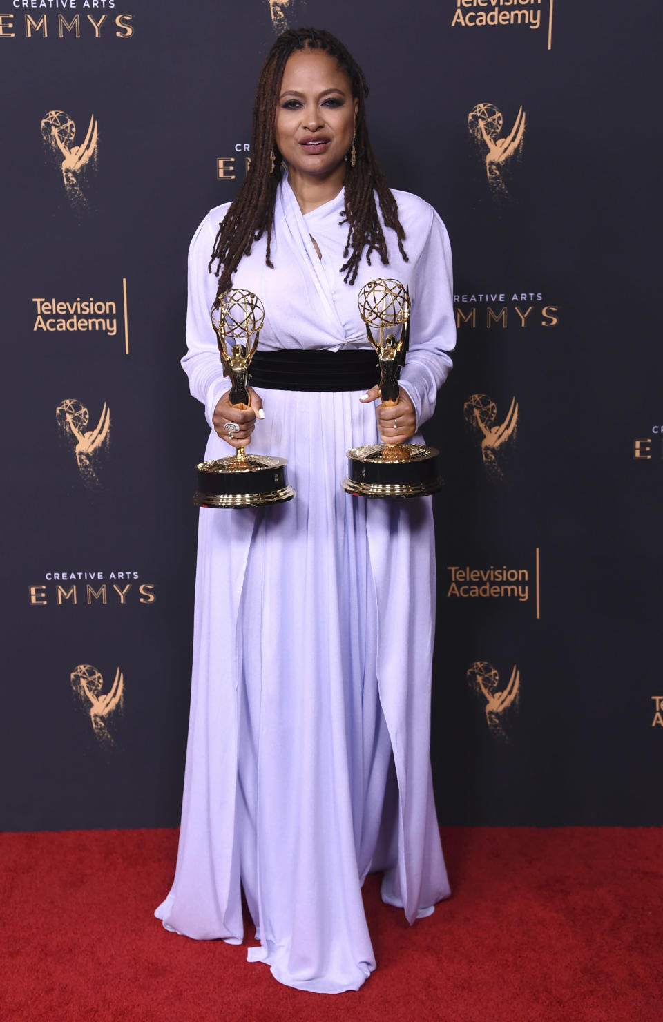 "FILE - Ava DuVernay, poses in the press room with the awards for outstanding documentary or nonfiction special, and for outstanding writing for nonfiction program for ""13th"" during night one of the Creative Arts Emmy Awards in Los Angeles on Sept. 9, 2017. DuVernay, who created the TV series ""Queen Sugar"" hired Cierra Glaude to work on the Oscar-nominated 2014 film ""Selma"" as well as her CBS pilot ""For Justice."" (Photo by Richard Shotwell/Invision/AP, File)"