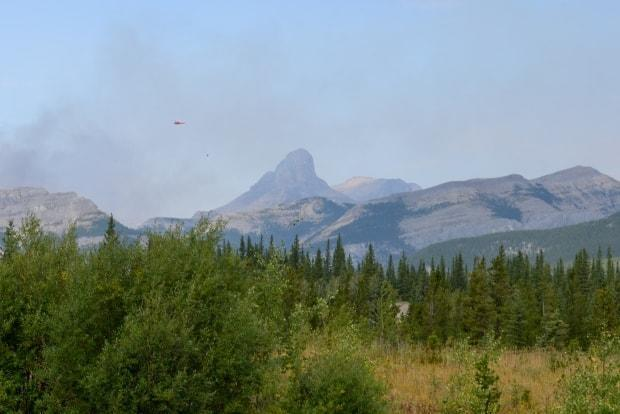 A smoky sky and a water bomber are seen overhead as an out-of-control wildfire burns near Banff National Park in this file photo from September 2020. With fire advisories, restrictions or bans in place across Alberta, officials are asking people to closely follow the rules during the current heat wave. (Helen Pike/CBC - image credit)