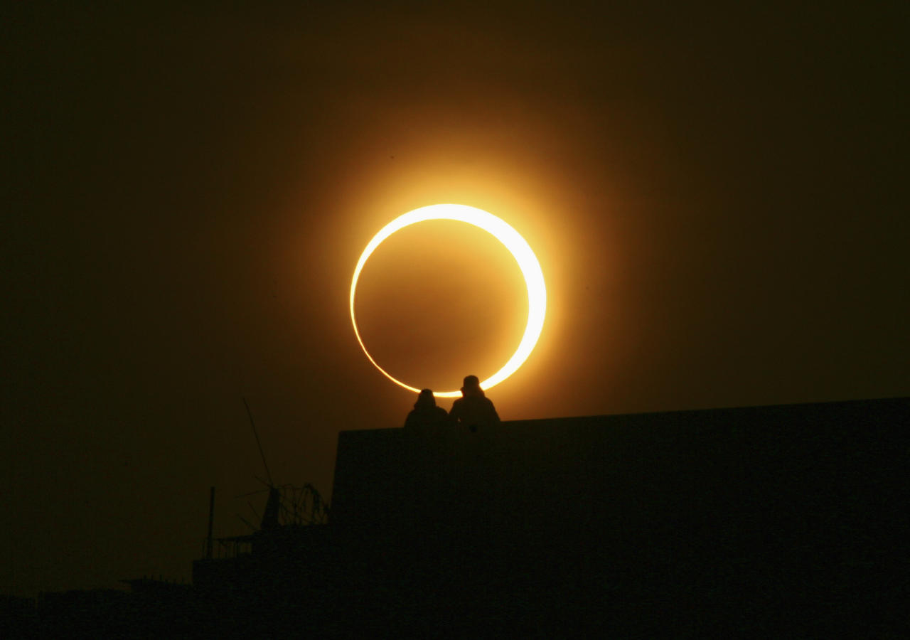 Two men sit on a bridge to watch an annular solar eclipse in Zhengzhou, Henan province, January 15, 2010. The longest, ring-like solar eclipse of the millennium started on Friday, with astronomers saying the Maldives was the best place to view the phenomenon that will not happen again for over 1,000 years. REUTERS/Donald Chan (CHINA - Tags: ENVIRONMENT SOCIETY)