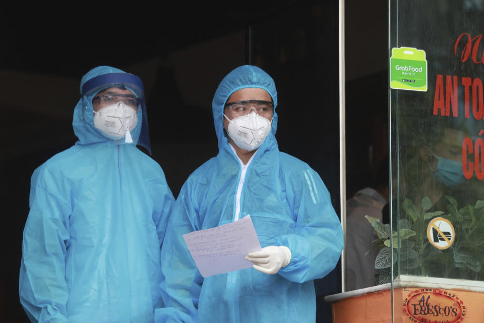 Health workers look out from a restaurant where a worker is suspected to have COVID-19 in Hanoi, Vietnam on Wednesday, July 29, 2020. Vietnam intensifies protective measures as the number of locally transmissions, starting at a hospital in the popular beach city of Da Nang, keeps increasing since the weekend. (AP Photo/Hau Dinh)