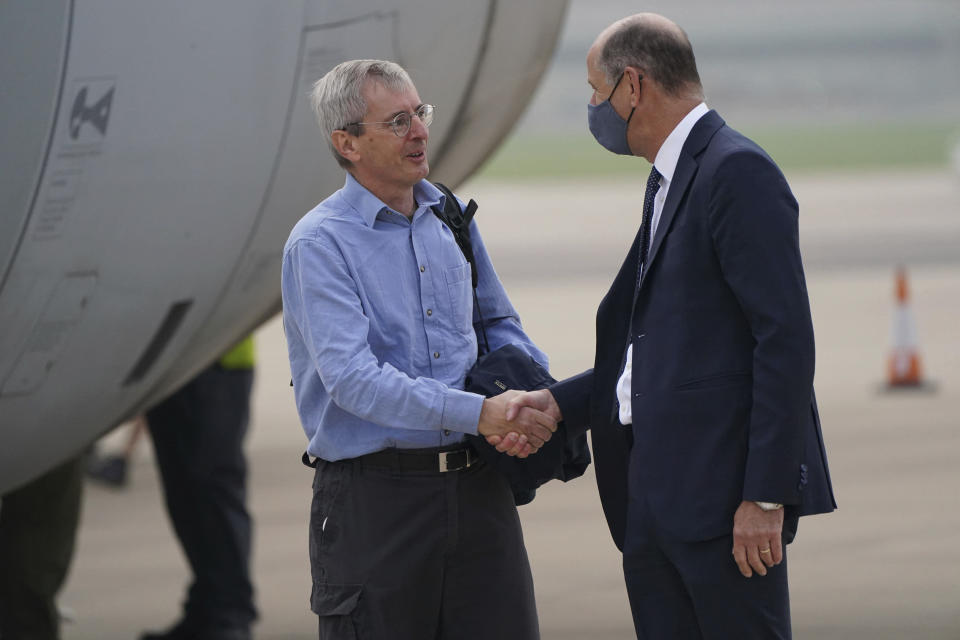 CAPTION CHANGES SOURCE TO POOL Britain's ambassador to Afghanistan, Laurie Bristow, left, is greeted by Philip Barton, Permanent Under-Secretary of the Foreign, Commonwealth and Development Office, as he exits a plane after being evacuated from Kabul, Afghanistan, upon its arrival at RAF Brize Norton base in Oxfordshire county, Britain, Sunday Aug. 29, 2021. Military planes carrying British troops and diplomats from Kabul are landing at a U.K. air base after the U.K.'s two-week evacuation operation ended. The U.K. ambassador to Afghanistan, Laurie Bristow, was among those who arrived Sunday at RAF Brize Norton northwest of London, hours after the government announced that all British personnel had left Kabul. (Jonathan Brady/Pool Photo via AP)