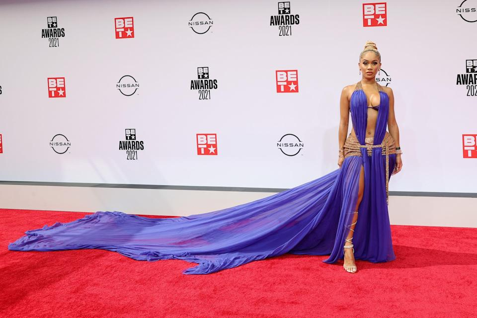 Saweetie rocked the red carpet in this plunging purple gown –complete with leg split and a train if we've ever seen one. The purple ensemble was accessorized with gold gladiator heels and Bulgari jewels.