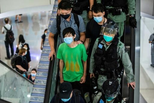 Police take away a man during a demonstration in a mall in Hong Kong in response to the new national security law