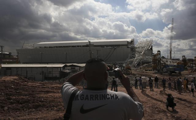 """A man records the crane that collapsed on the site of the Arena Sao Paulo stadium, known as """"Itaquerao"""", which will host the opening soccer match of the 2014 World Cup, in Sao Paulo November 27, 2013. A crane collapsed on Wednesday at the construction site of a future World Cup soccer stadium in Sao Paulo, Brazil, killing at least three people and causing damage to the structure, local media said. REUTERS/Nacho Doce (BRAZIL - Tags: SPORT SOCCER WORLD CUP)"""