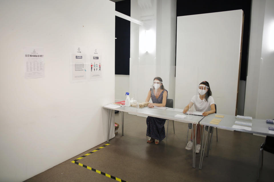 People wearing face mask and visor to protect against coronavirus sit behind a glass shield during a rehearsal of the vote for the local elections scheduled for Sunday, June 28, in Paris, Friday, June 26, 2020. France is to hold its Covid-19 delayed second round of local elections on June 28. (AP Photo/Thibault Camus)