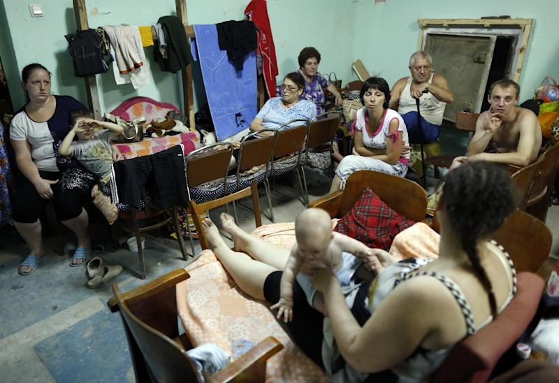 Photo taken on August 13, 2014 shows people inside a makeshift bomb shelter in the basement of their house in the town of Yasynuvata near Donetsk, eastern Ukraine
