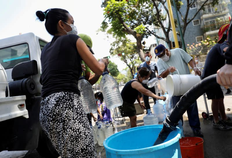 FILE PHOTO: People collect water on a street in Caracas during the coronavirus pandemic