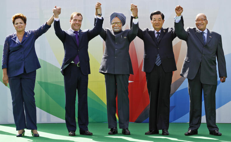 From left to right, Brazil's President Dilma Rousseff, Russian President Dmitry Medvedev, Indian Prime Minister Manmohan Singh, Chinese President Hu Jintao and South African President Jacob Zuma raise their arms together during the group picture for the BRICS 2012 Summit in New Delhi, India, Thursday, March 29, 2012. Heads of States of the five nations are meeting in the Indian capital Thursday. (AP Photo/Saurabh Das)