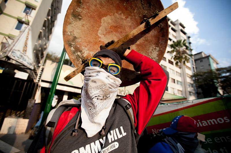 A demonstrator covers himself with a home made shield after policemen fired teargas during clashes in an anti-government protest in Caracas, Venezuela, Monday, March 10, 2014. The Venezuelan government and opposition appear to have reached a stalemate, in which street protests continue almost daily while the opposition sits out a peace process it calls farcical. (AP Photo/Alejandro Cegarra)