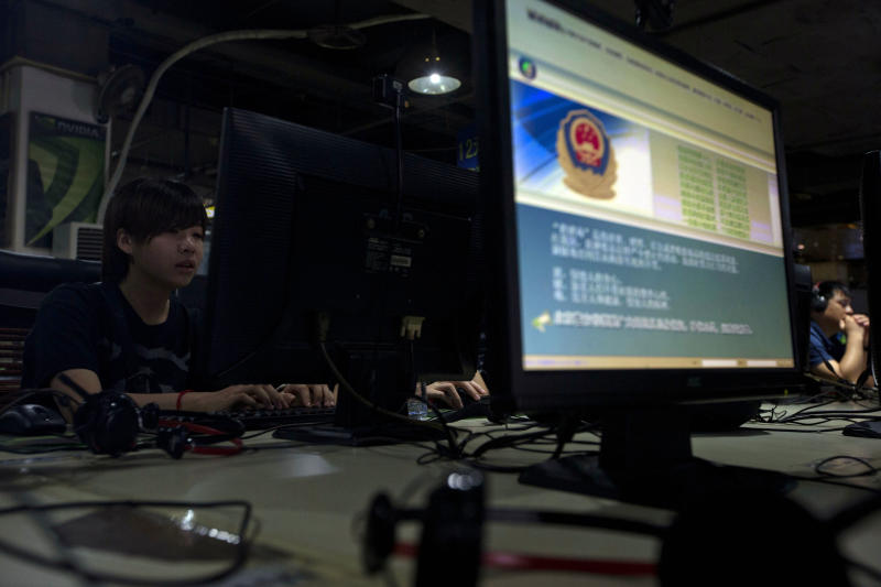 """Computer users sit near a display with a message from the Chinese police on the proper use of the internet at an internet cafe in Beijing, China, Monday, Aug. 19, 2013. China's newest opinion leaders - ranging from pop stars to scholars, journalists to business tycoons - exert their influence via microblogs known as """"Big Vs'' because the accounts are ''verified'' and popular. Authorities are now tightening the screws on these latest additions to the country's already constricted information stream. (AP Photo/Ng Han Guan)"""