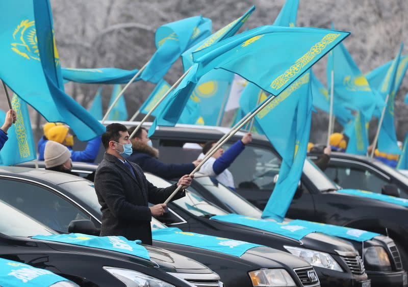 Supporters of the Nur Otan ruling party wave national flags during a pre-election rally in Almaty