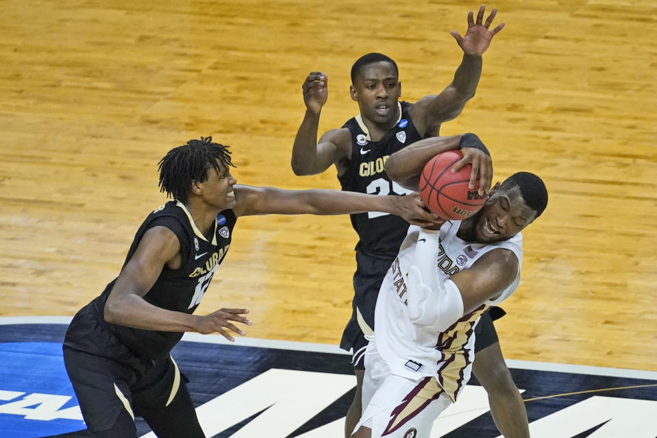 Colorado forward Jabari Walker, left, fouls Florida State forward RaiQuan Gray, right, as Colorado guard McKinley Wright IV (25) closes in during the second half of a second-round game in the NCAA college basketball tournament at Farmers Coliseum in Indianapolis, Monday, March 22, 2021. (AP Photo/Charles Rex Arbogast)