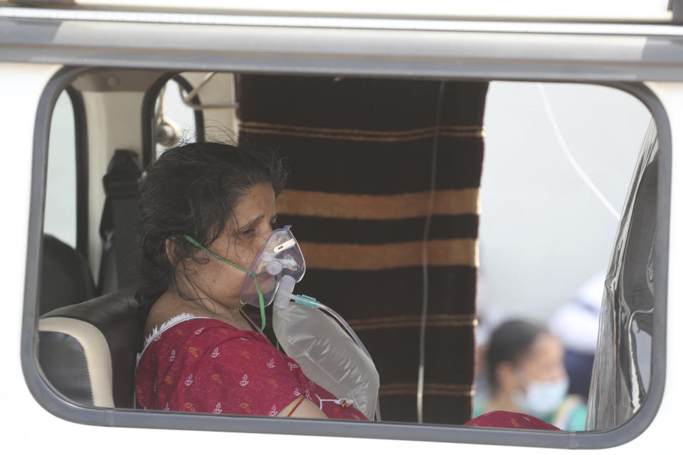 A COVID-19 patient waits inside an ambulance to be attended to and admitted into a dedicated COVID-19 government hospital in Ahmedabad, India, Thursday, April 22, 2021. A fire killed 13 COVID-19 patients in a hospital in western India early Friday as an extreme surge in coronavirus infections leaves the nation short of medical care and oxygen. India reported another global record in daily infections for a second straight day Friday, adding 332,730 new cases. The surge already has driven its fragile health systems to the breaking point with understaffed hospitals overflowing with patients and critically short of supplies. (AP Photo/Ajit Solanki)