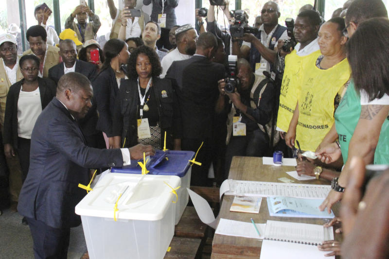 FILE - In this Tuesday, Oct. 15, 2019 file photo, Mozambican President Felipe Nyusi,left, casts his vote in Maputo in the country's elections. Nyusi is to be sworn in Wednesday, Jan. 15, 2020 for a second and final term in Maputo after five turbulent years in office and facing two armed insurgencies as well as economic opportunities. (AP Photo/Ferhat Momade/File)