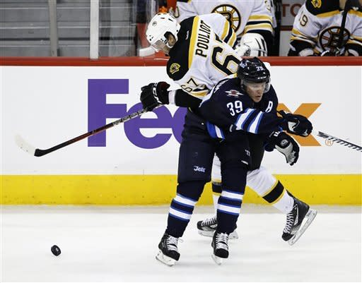 Winnipeg Jets' Tobias Enstrom (39) bumps Boston Bruins' Benoit Pouliot (67) off the puck during the second period of an NHL hockey game, Friday, Feb. 17, 2012, in Winnipeg, Manitoba. (AP Photo/The Canadian Press, Trevor Hagan)