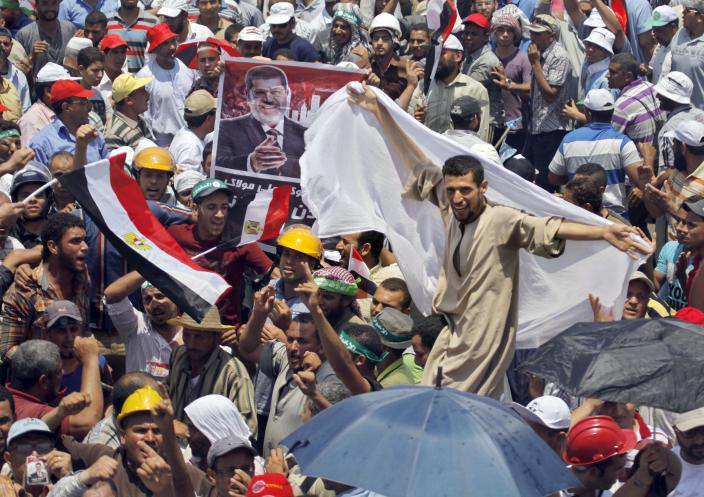 An Egyptian supporter of Egypt's Islamist President Mohammed Morsi dances by a poster of Morsi during a rally outside the Rabia el-Adawiya mosque near the presidential palace in Cairo, Saturday, June 29, 2013. Thousands of supporters and opponents of Egypt's embattled Islamist president held rival sit-ins in separate parts of Cairo Saturday on the eve of opposition-led mass protests aimed at forcing Mohammed Morsi from power. (AP Photo/Amr Nabil)