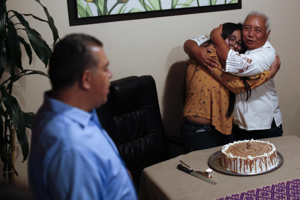 Ximena Canejo Hernandez is embraced by her grandmother Eloisa Santos Castillo, as close relatives gathered for a simple event at home to mark Ximena's 15th birthday, in Tlalnepantla, just outside Mexico City, Monday, July 13, 2020. Ximena's family, wanting to give her a traditional Quinceanera, had booked a church and event hall for July 18th long before the coronavirus pandemic hit, but the celebration had to be postponed until late November. The family had been following stay at home guidance, but with Mexico City's opening beginning in recent weeks, Ximena's grandmother decided to travel up from Oaxaca for her birthday, the first visit to her daughters and grandchildren in more than four months. (AP Photo/Rebecca Blackwell)