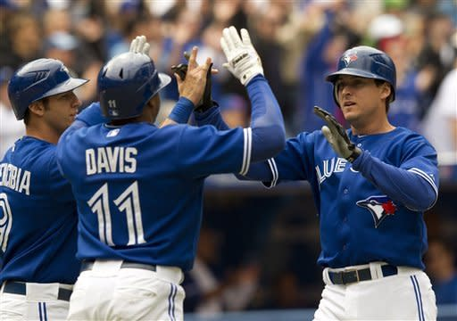 Toronto Blue Jays' Kelly Johnson, right, J.P. Arencibia and Rajai Davis (11) celebrate after scoring on teammate Yune Escobar's bases loaded triple during the fourth inning of a baseball game against the Texas Rangers on Wednesday, May 2, 2012, in Toronto. (AP Photo/The Canadian Press, Frank Gunn)