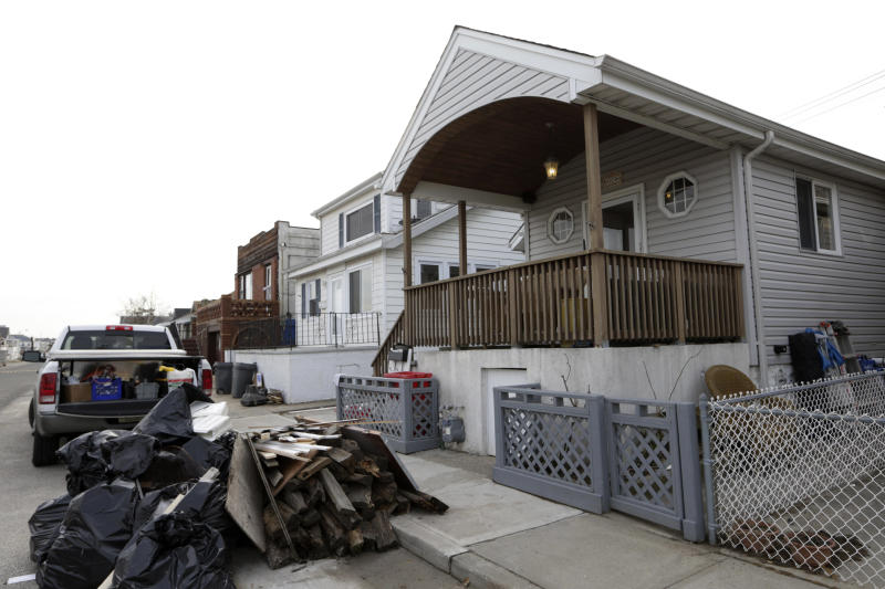 Trash is piled up outside the Troy family home in Long Beach, N.Y., Wednesday, Dec. 12, 2012, as workers redo the interior after Superstorm Sandy's surge did serious damage there. Donald Denihan, who endured three near-death experiences, is paying for repairs while the Troy family stays in nearby Point Lookout, at the second house of another generous family. (AP Photo/Kathy Willens)