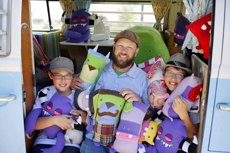 This photo taken on May 23, 2013 shows Ray Tollison, center, with his twin sons, Ben, left, and Sam posing with monster dolls in their van at their home in Fort Collins, Colo. The Tollisons launched Monster to Love, a company that makes plush monster toys. (AP Photo/Ed Andrieski)