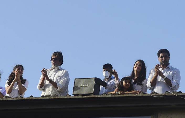 Bollywood actors Amitabh Bachchan (2L) and his son Abhishek Bachchan (R) with wife Aishwarya Rai Bachchan (2R) along with their daughter Aaradhya (3R) clap from atop a residential building to thank essential service providers during a one-day Janata (civil) curfew imposed amid concerns over the spread of the COVID-19 novel coronavirus, in Mumbai on March 22, 2020. (Photo by Sujit Jaiswal / AFP) (Photo by SUJIT JAISWAL/AFP via Getty Images) / Credit: SUJIT JAISWAL