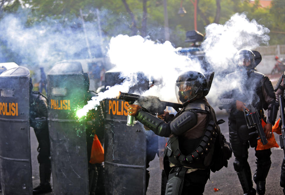 A police officer fires his tear gas launcher during a clash with student protesters in Surabaya, East Java, Indonesia, Thursday, Oct. 8, 2020. Thousands of enraged students and workers staged rallies across Indonesia on Thursday in opposition to the new law they say will cripple labor rights and harm the environment. (AP Photo/Trisnadi)