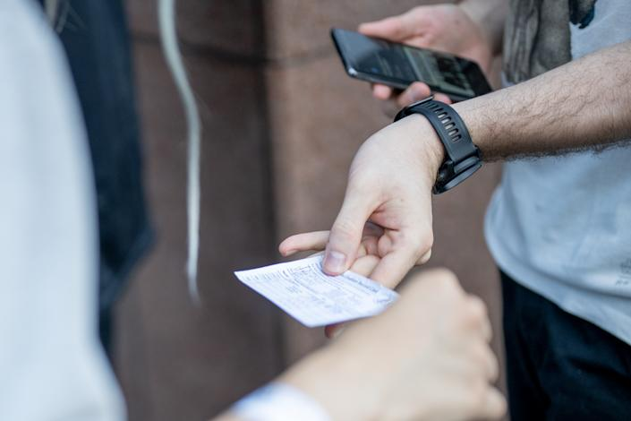 A person presents his proof of vaccination while standing in line for the Foo Fighters show as Madison Square Garden reopens with the first full capacity concert since March 2020 on June 20, 2021 in New York City. (Roy Rochlin/Getty Images)