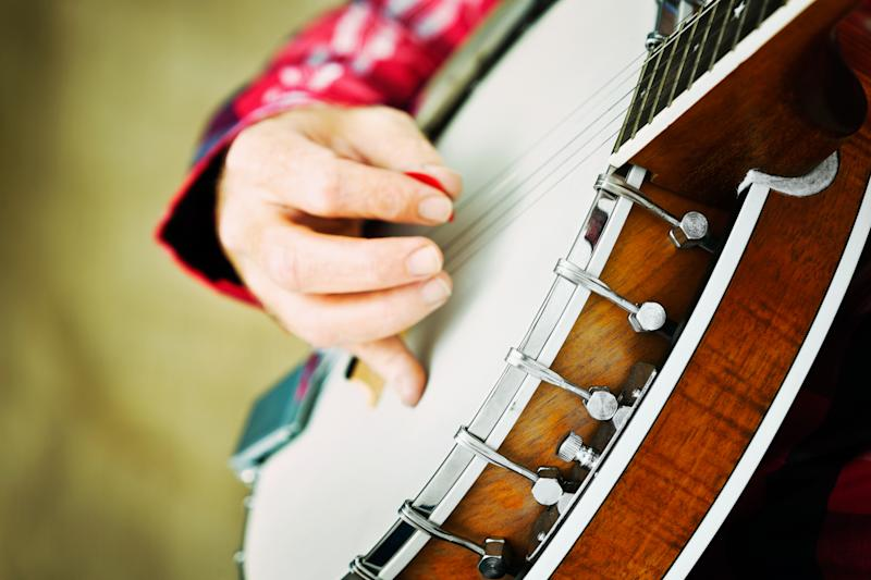 Cropped shot of a banjo being played with a pick (or plectrum) by a feminine hand.