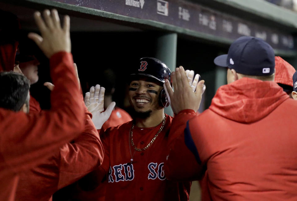 Boston Red Sox's Mookie Betts celebrates in the dugout after scoring of a single by Steve Pearce during the third inning of Game 1 of a baseball American League Division Series against the New York Yankees on Friday, Oct. 5, 2018, in Boston. (AP Photo/Charles Krupa)