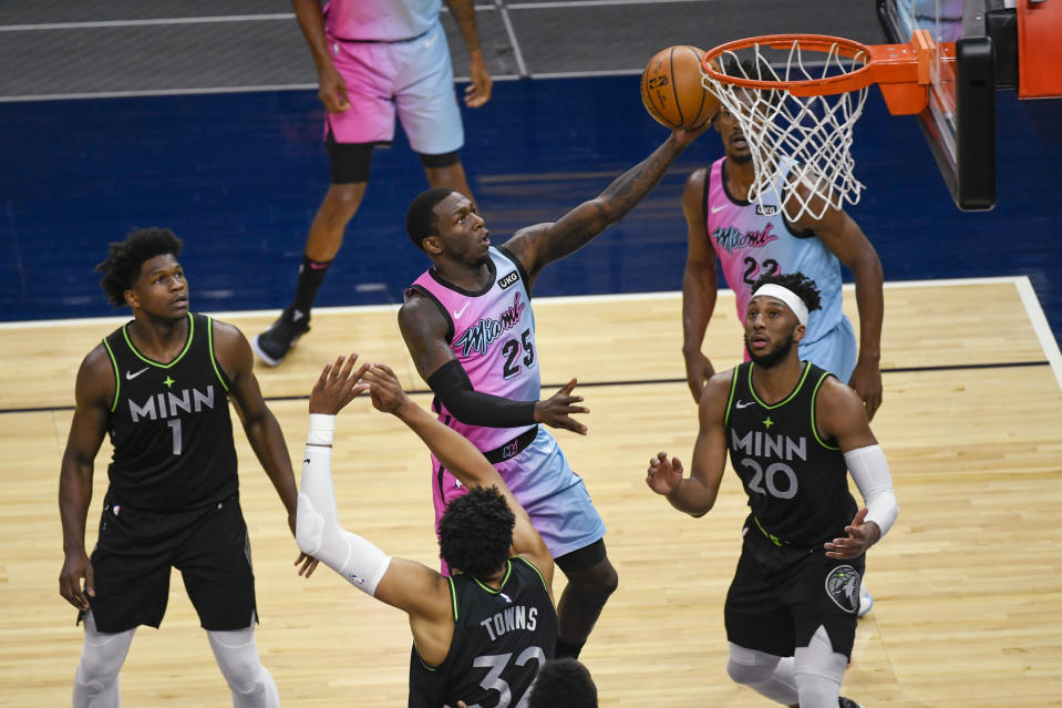 Miami Heat guard Kendrick Nunn (25) goes up for a shot past Minnesota Timberwolves guard Anthony Edwards (1), center Karl-Anthony Towns (32) and forward Josh Okogie (20) during the first half of an NBA basketball game Friday, April 16, 2021, in Minneapolis. (AP Photo/Craig Lassig)