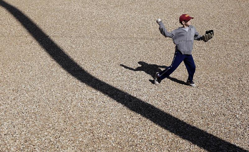 Tyler Adkison, 9, of San Diego, Calif., throws the ball to his father while waiting to get autographs from the Cleveland Indians during a spring training baseball workout in Goodyear, Ariz., Friday, March 2, 2012. (AP Photo/Jae C. Hong)
