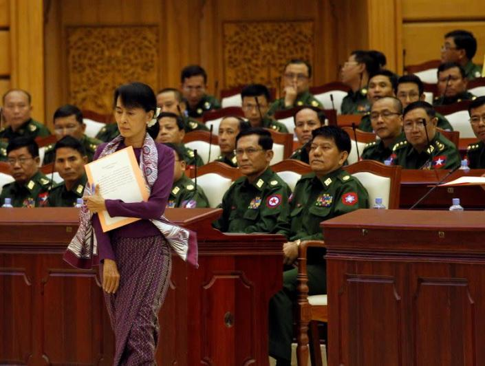 FILE PHOTO: Aung San Suu Kyi walks to take an oath at the lower house of parliament in Naypyitaw