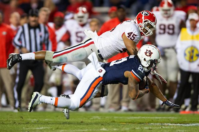 AUBURN, AL - NOVEMBER 10: Running back Tre Mason #21 of the Auburn Tigers goes airborne after being hit by linebacker Christian Robinson #45 of the Georgia Bulldogs on November 10, 2012 at Jordan-Hare Stadium in Auburn, Alabama. Georgia defeated Auburn 38-0 and clinched the SEC East division. (Photo by Michael Chang/Getty Images)