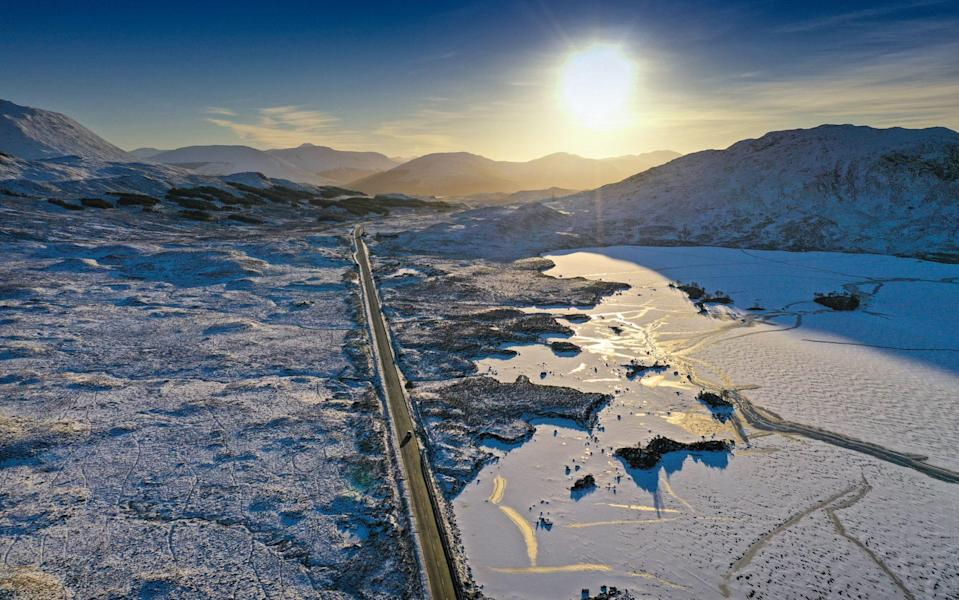 A vehicle travels on the A82 past a frozen over Lochan na Achlaise as freezing temperatures continue in Glen Coe - Getty
