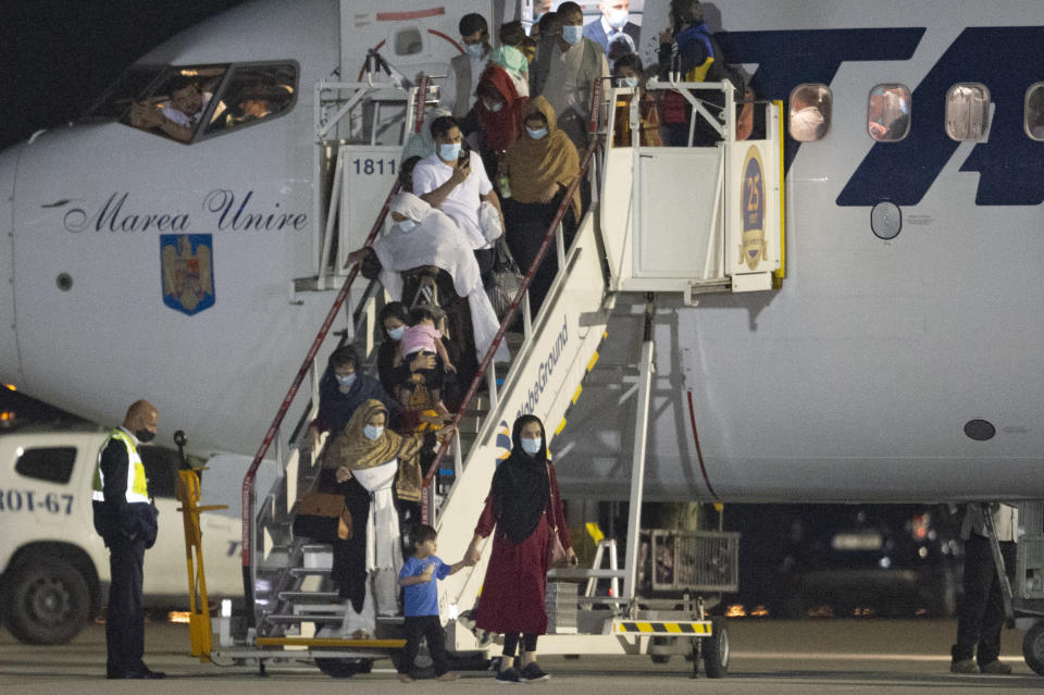 Afghan citizens evacuated by Romanian authorities from Afghanistan disembark an airplane at the Baza 90 military base after being flown in from Pakistan in Otopeni, near Bucharest, Romania, Thursday, Sept. 9, 2021. The Romanian Foreign Ministry organized the evacuation of 156 Afghan citizens, former aides of the Romanian military that operated in Afghanistan, students, human rights activists, journalists, magistrates and their family members, of which 139 arrived to Romania on Thursday night. (AP Photo/Alexandru Dobre)