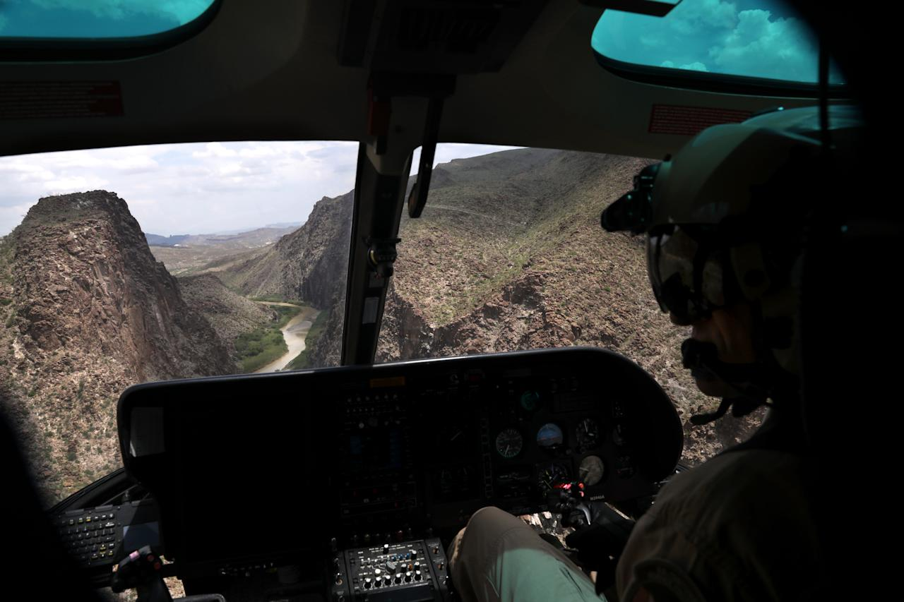 <p>A U.S. Customs and Border Protection pilot does a helicopter patrol along the U.S.-Mexico border on Aug. 1, 2017, near Lajitas, Texas. Logistical challenges, such as the rugged terrain of west Texas's Big Bend region, are just some of the complications to building the border wall proposed by President Trump. (Photo: John Moore/Getty Images) </p>