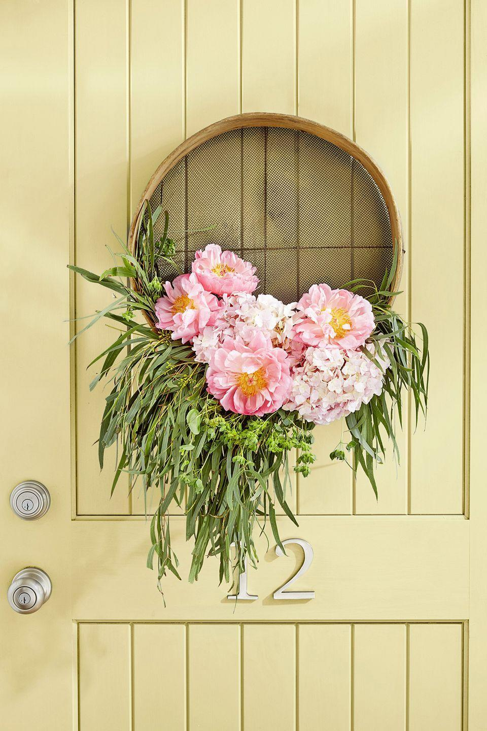 "<p>Put a vintage grain sifter to good use by making it into fresh home decor. Take floral tubes, fill with water, insert flowers, and attach to the sifter with wire. Loop the wire to hang on the front door.</p><p><a class=""link rapid-noclick-resp"" href=""https://go.redirectingat.com?id=74968X1596630&url=https%3A%2F%2Fwww.etsy.com%2Flisting%2F722850955%2Fbig-10antique-wooden-sieve-vintage&sref=https%3A%2F%2Fwww.countryliving.com%2Fdiy-crafts%2Fg4395%2Fsummer-wreaths%2F"" rel=""nofollow noopener"" target=""_blank"" data-ylk=""slk:SHOP GRAIN SIFTERS"">SHOP GRAIN SIFTERS</a></p>"