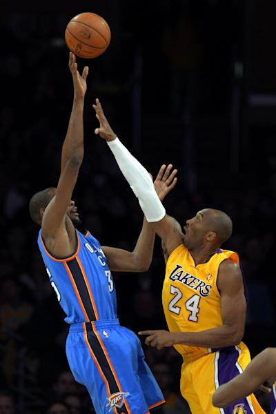 Oklahoma City Thunder forward Kevin Durant, left, shoots over Los Angeles Lakers guard Kobe Bryant during the first half of their NBA basketball game, Friday, Jan. 11, 2013, in Los Angeles. (AP Photo/Mark J. Terrill)