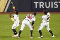 Atlanta Braves center fielder Ronald Acuna Jr., from left, right fielder Nick Markakis and center fielder Cristian Pache celebrate their win against the Los Angeles Dodgers in Game 4 of a baseball National League Championship Series Thursday, Oct. 15, 2020, in Arlington, Texas. (AP Photo/Tony Gutierrez)